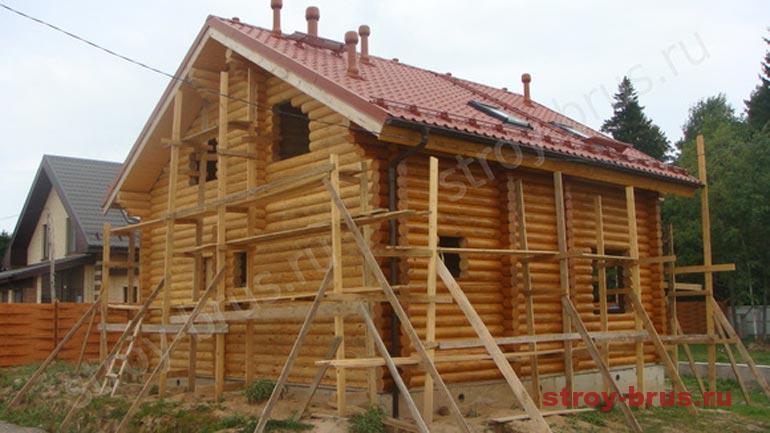 Процесс покраски фасада дома из оцилиндрованного бревна