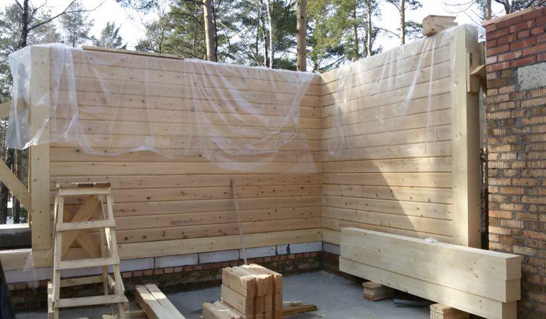 Брус для строительства экологичного дома укрывается от атмосферных осадков во время строительства