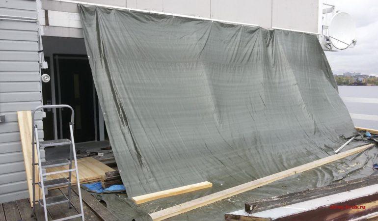 Строительная зона реконструкции стены защищена от осадков